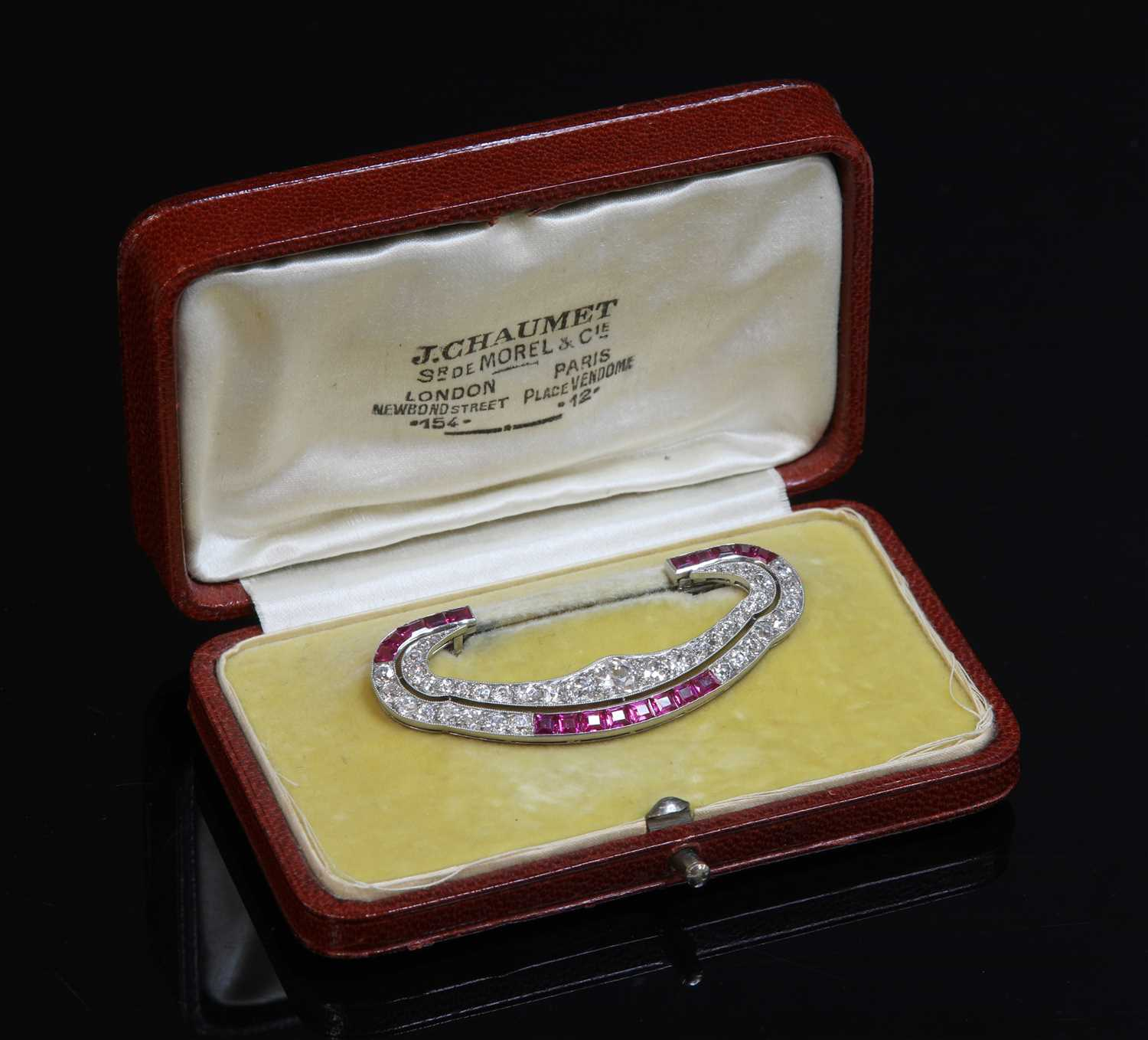 Lot 199 - A cased Art Deco platinum and gold, ruby and diamond brooch attributed to Chaumet c.1930,