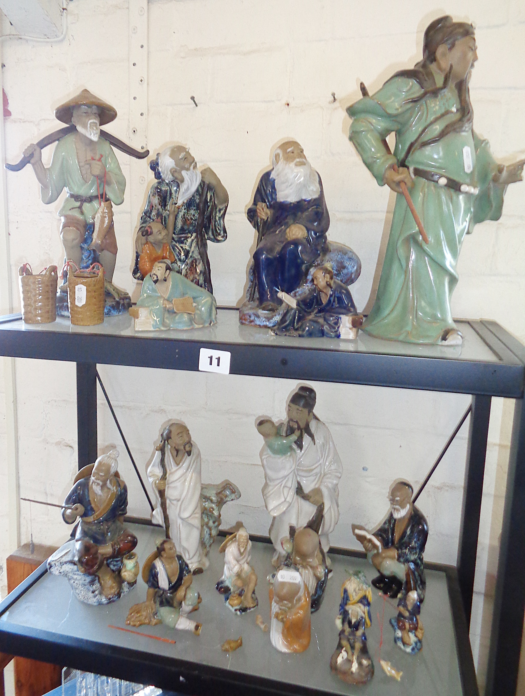 """Lot 11 - Collection of Japanese glazed pottery """"Mud-men"""" figures of peasants and scholars"""