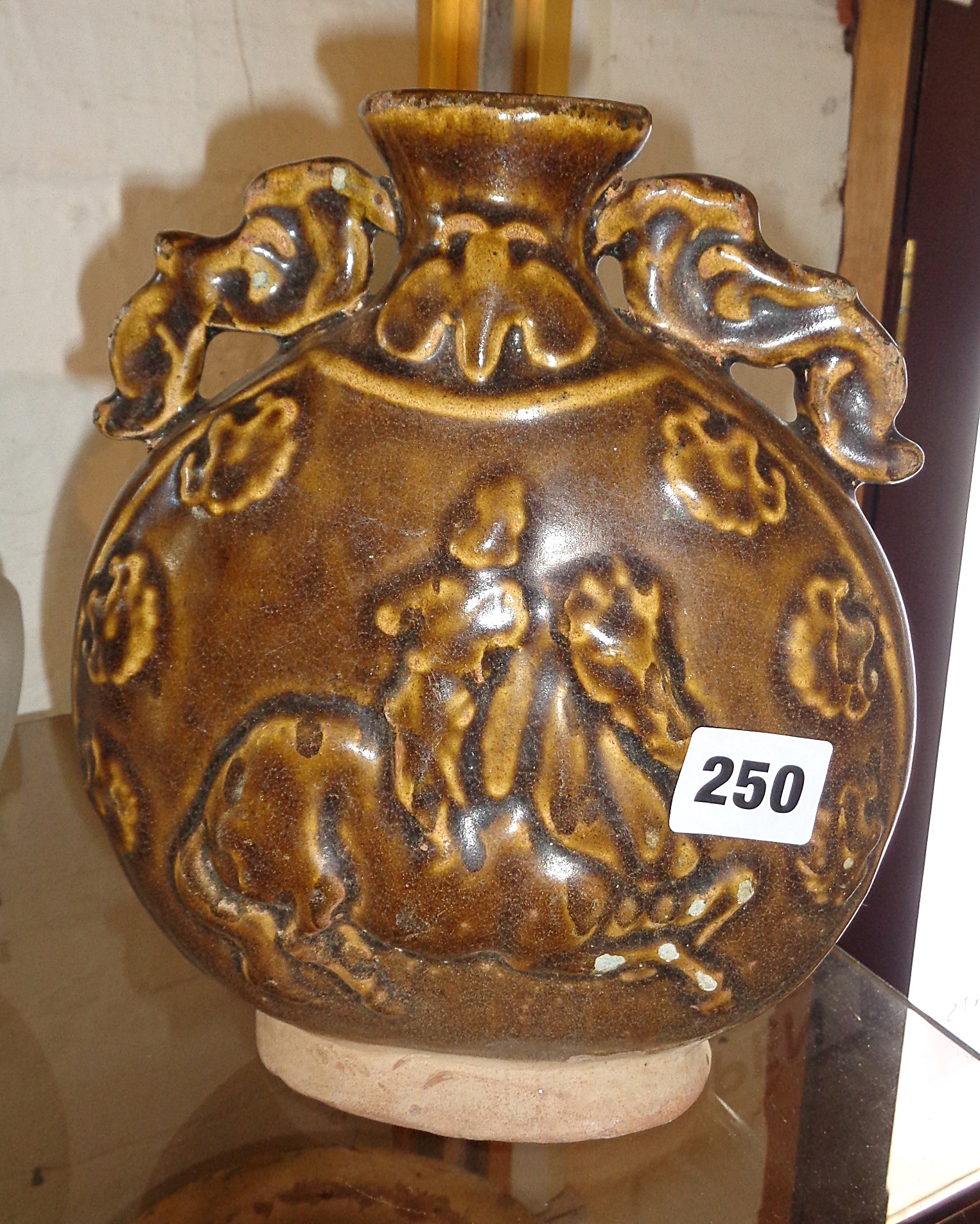 Lot 250 - Chinese moon flask with raised horse and rider decoration, in brown treacle glaze