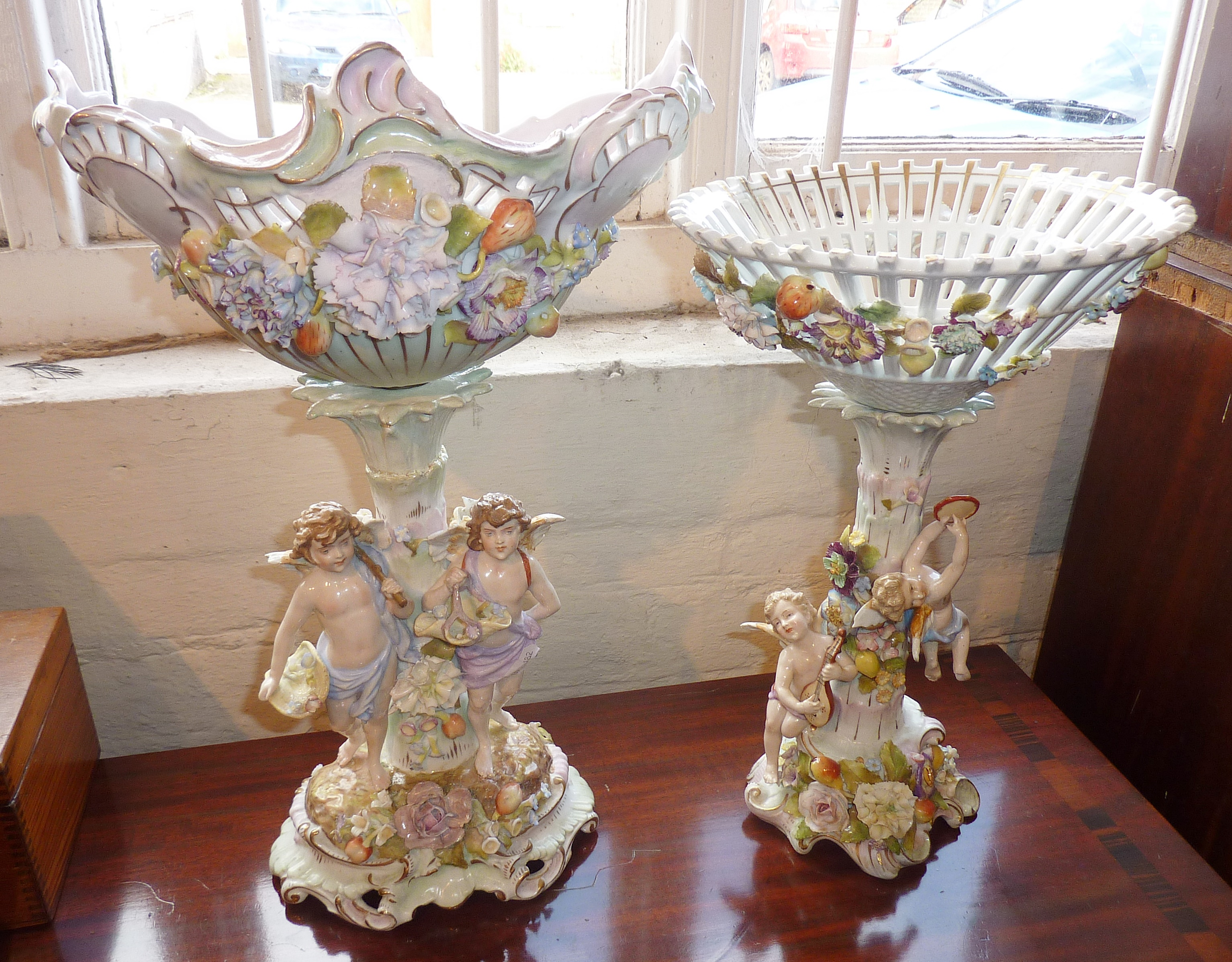 Lot 282 - Austrian or German porcelain figural centrepieces, decorated with cherubs and flowers (both