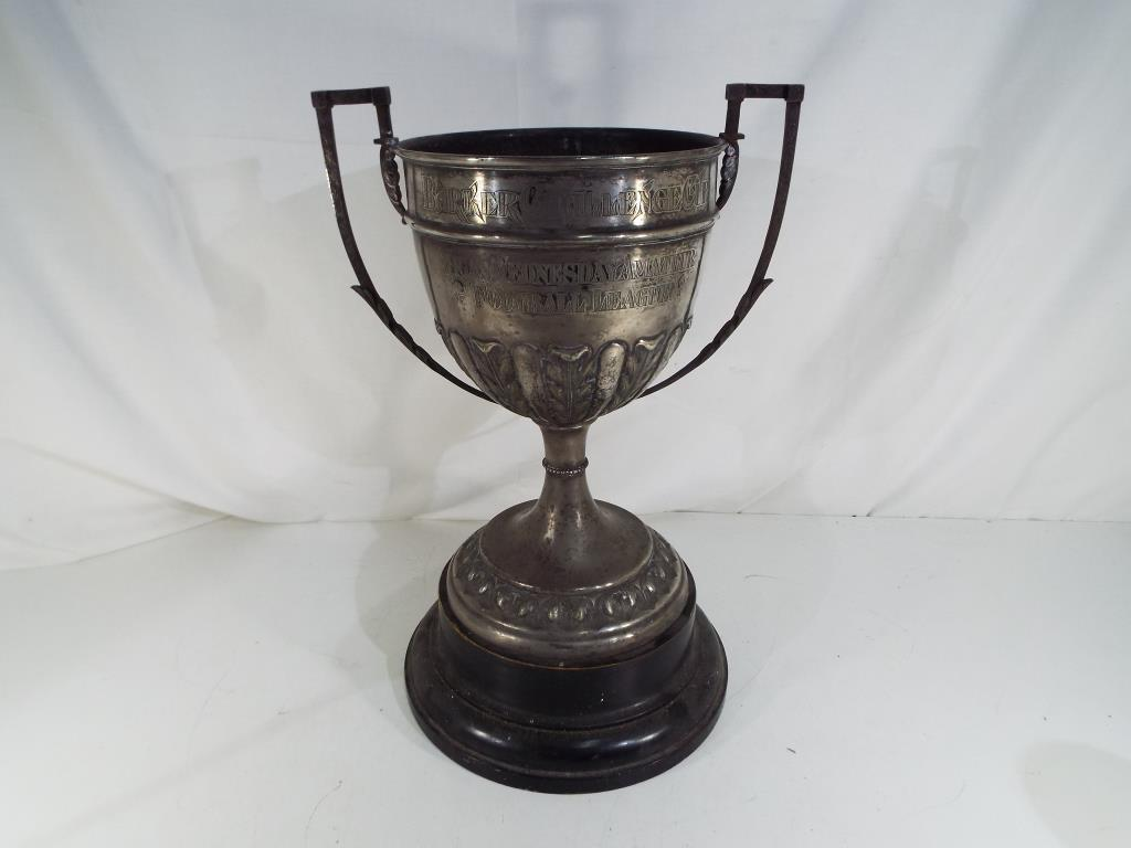Lot 18 - A vintage twin handled trophy with foliate decoration on an ebonised base engraved Barker Challenge