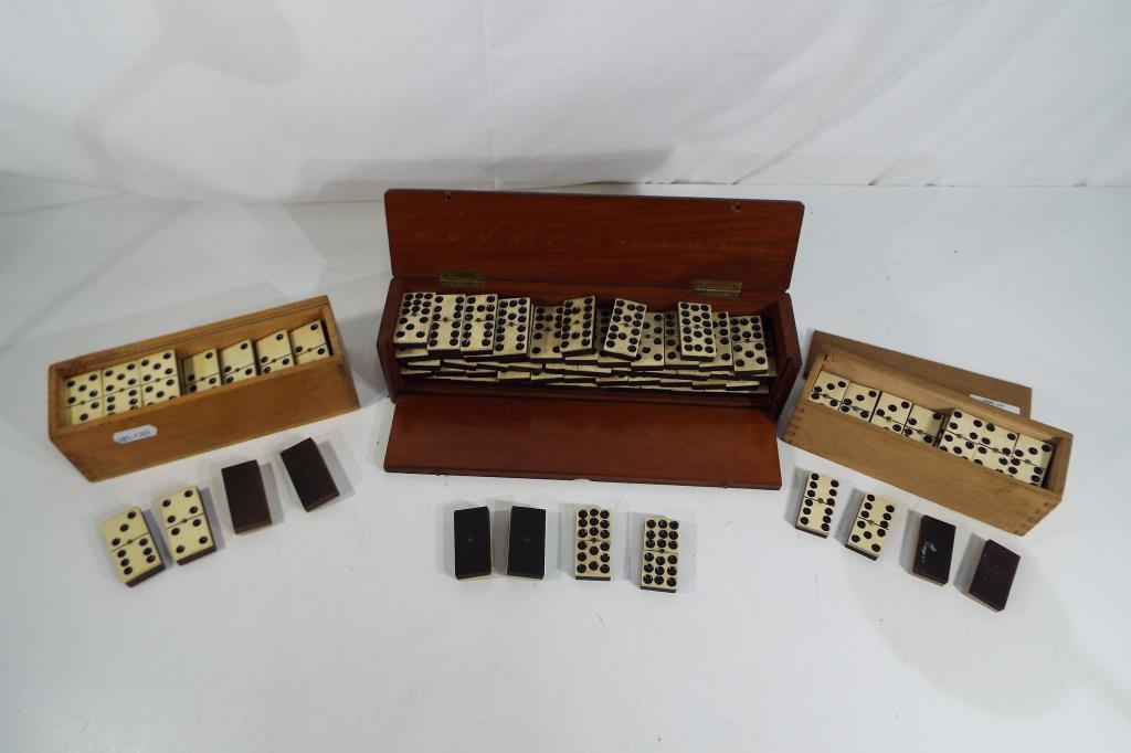 Lot 13 - Three wood cased sets of vintage dominoes comprising a bone and ebony double nine set with spinners