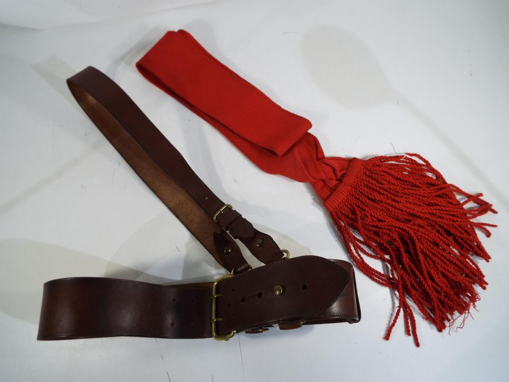 Lot 34 - An officer's belt with shoulder strap and red sash.
