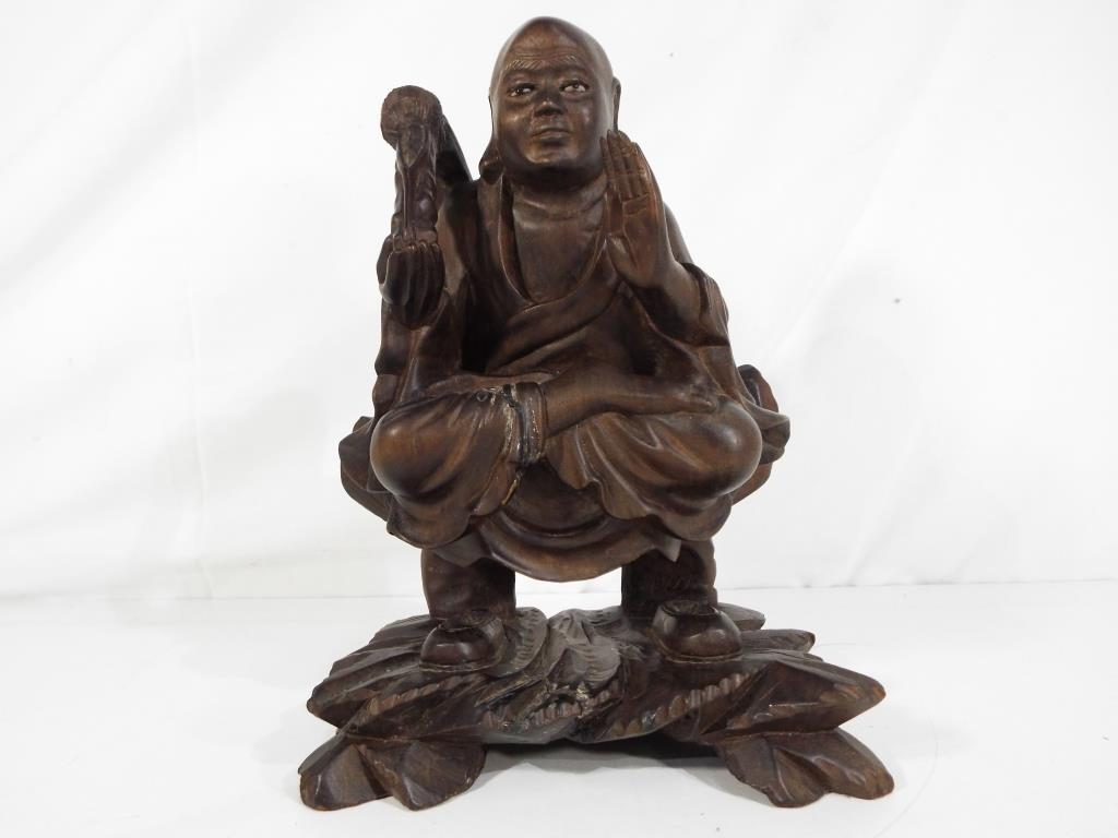 Lot 32 - An Oriental hardwood carving depicting a seated Buddha having glass eyes,