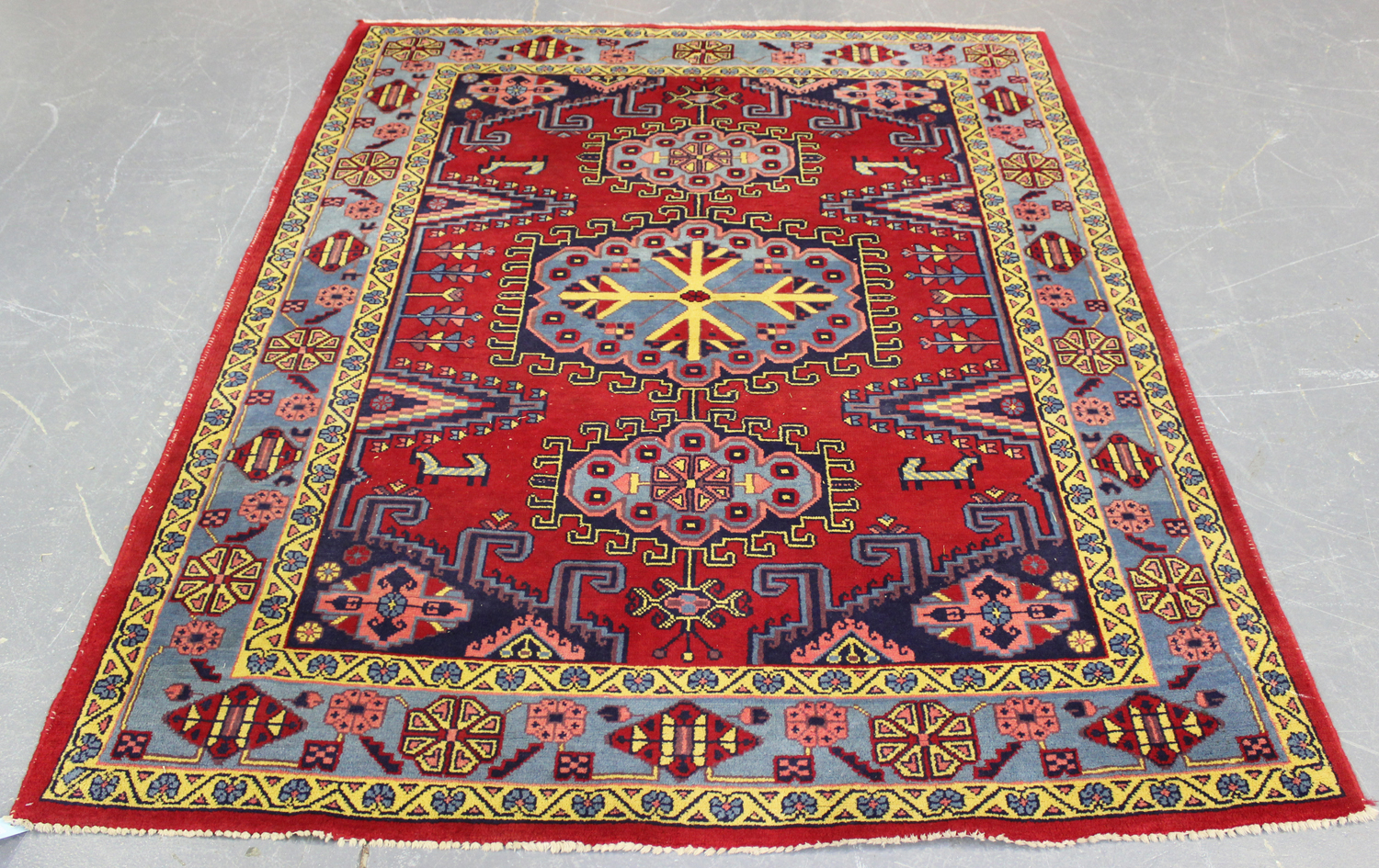 Lot 2920 - A Persian rug, mid/late 20th century, the red field with a hooked blue medallion, within a pale blue