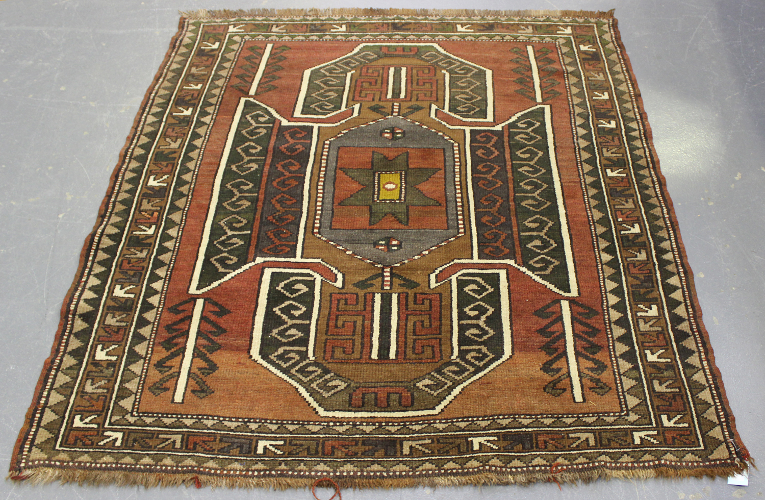 Lot 2924 - A Turkish 'Kazak' design rug, mid-20th century, the shaded claret field with a large shaped