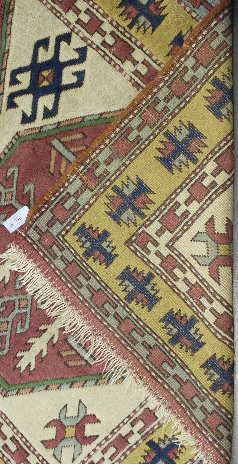 Lot 2911 - A Turkish rug, late 20th century, the ivory field with two bold medallions, within a yellow