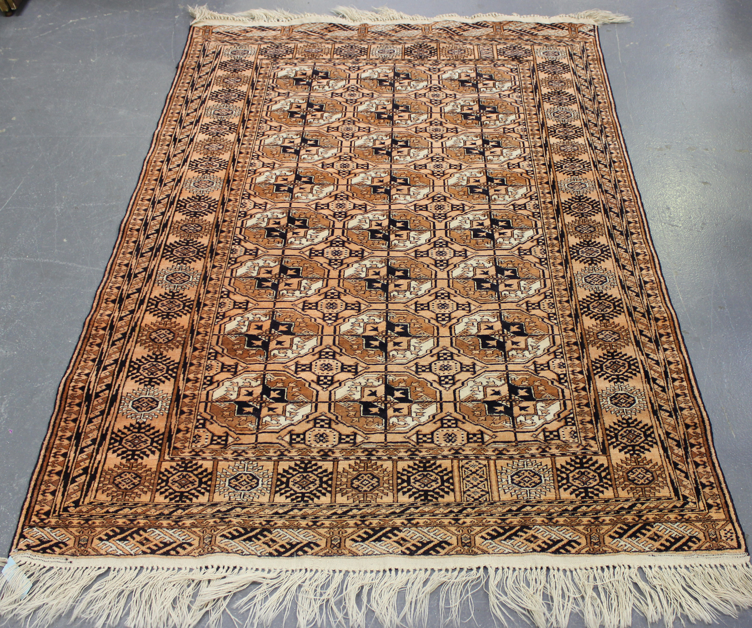 Lot 2928 - A Pakistan bokhara rug, mid-20th century, the pink field with three columns of guls, within a