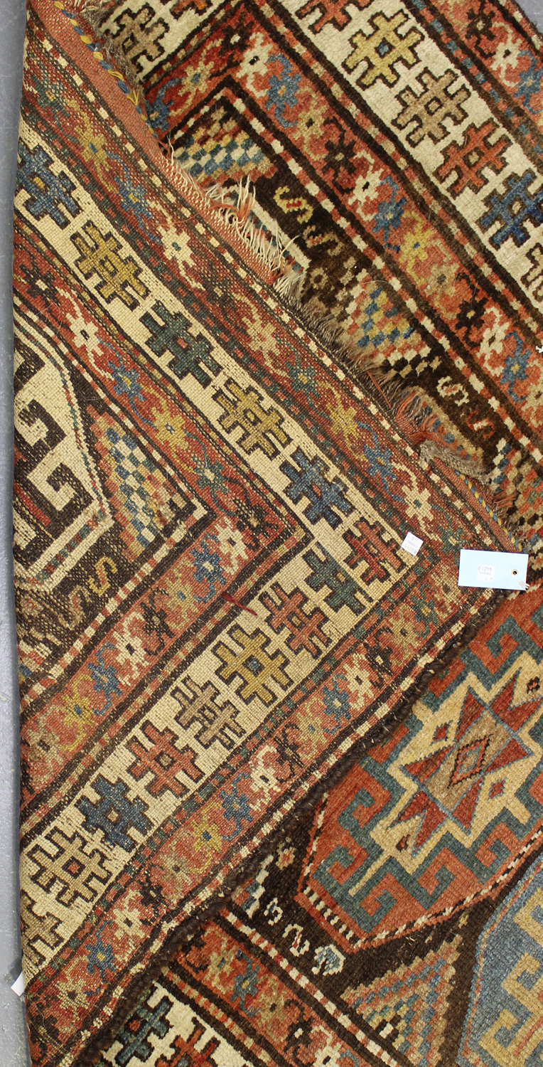 Lot 2927 - A Kurdish runner, early 20th century, the brown field with a single column of polychrome medallions,