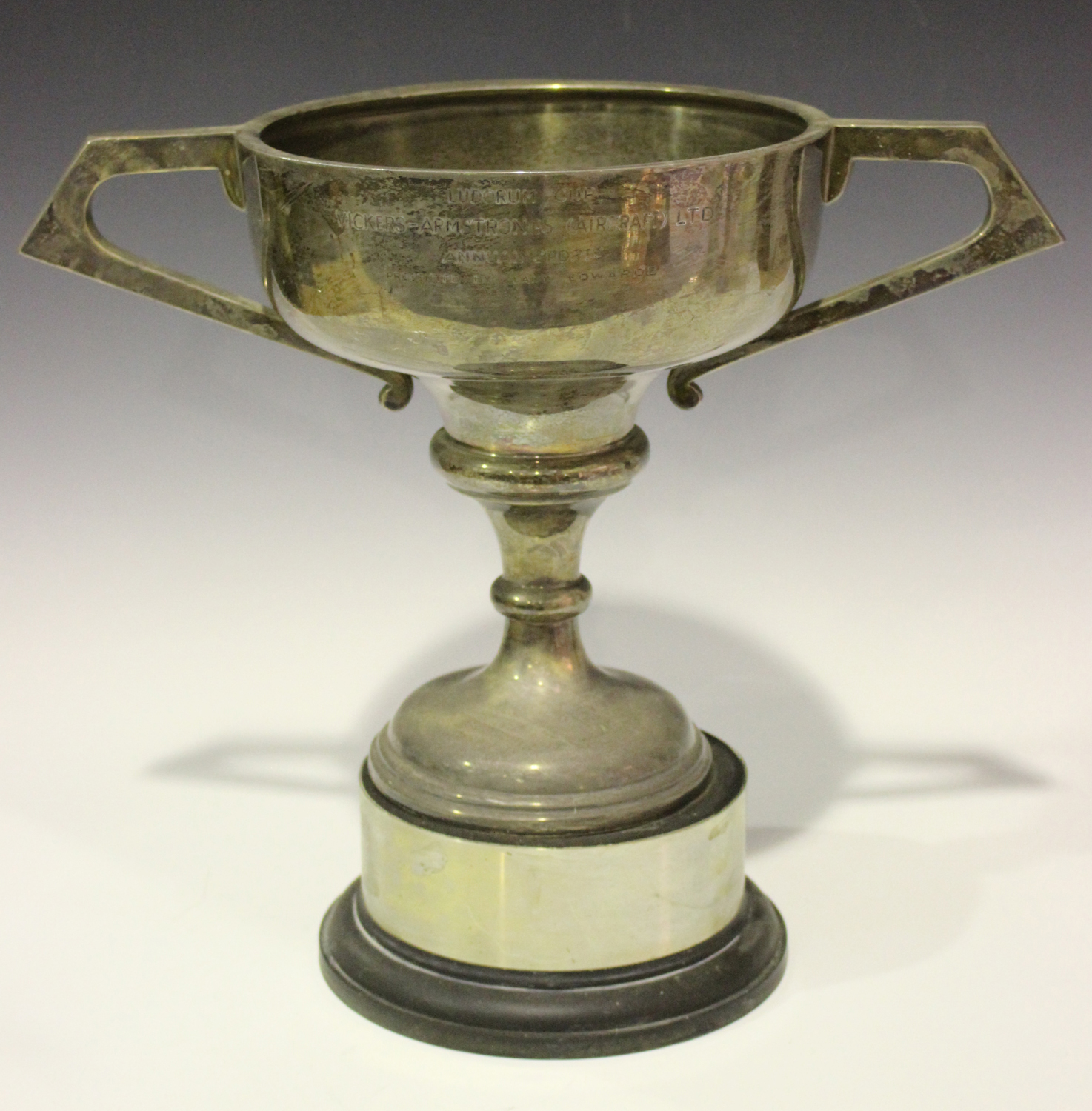 Lot 469 - A large Elizabeth II two-handled silver trophy cup, the ogee bowl flanked by angular handles, raised