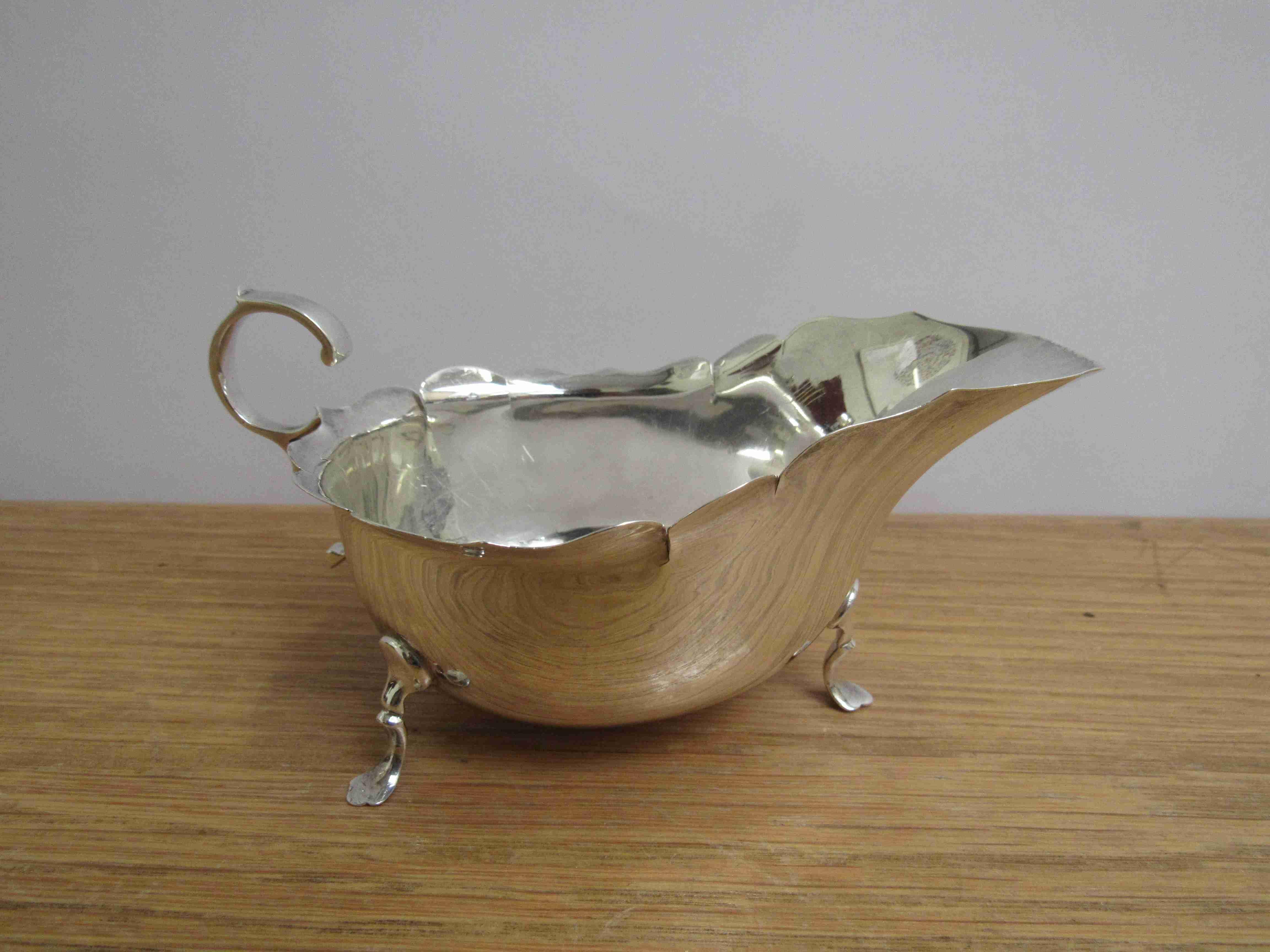 Lot 42 - A Martin Hall & Co Ltd silver sauce boat, shaped rim, scroll handle, three feet, Sheffield 1914,