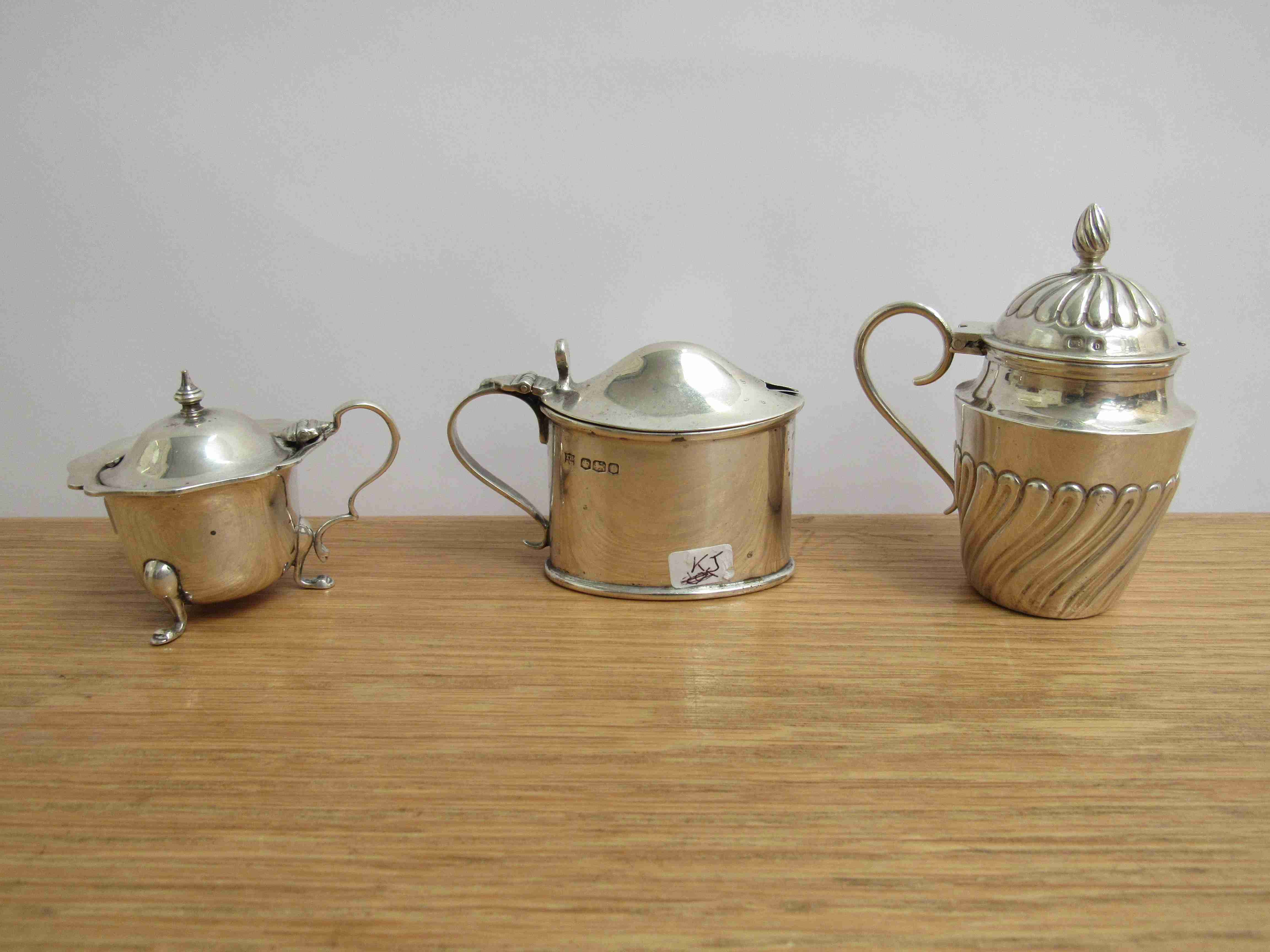 Lot 1 - Three silver mustard pots including Wrythen pattern Hilliard & Thomason, Birmingham 1901,