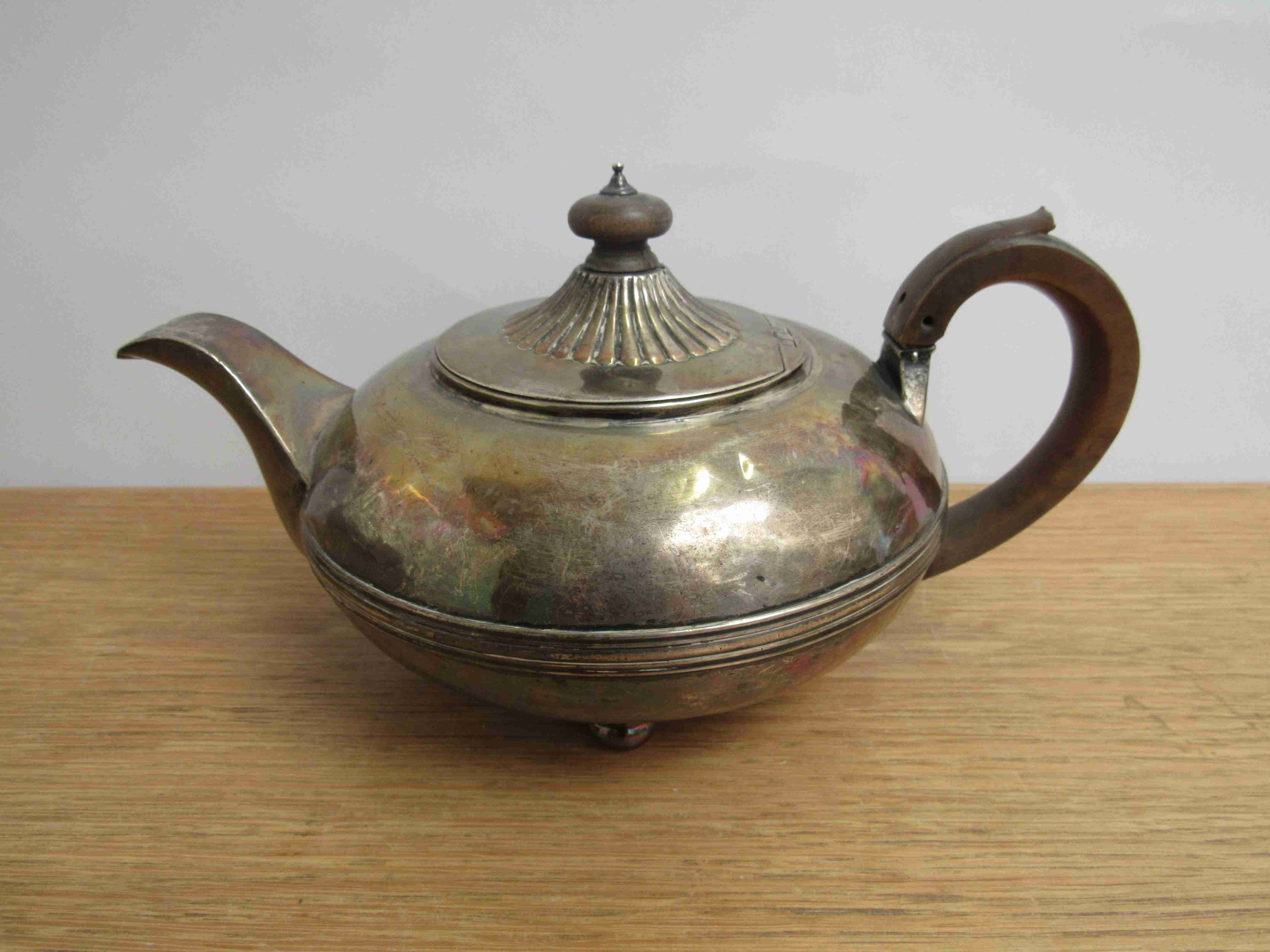Lot 13 - A Georgian silver teapot with treen finial and handle marks rubbed, dented,