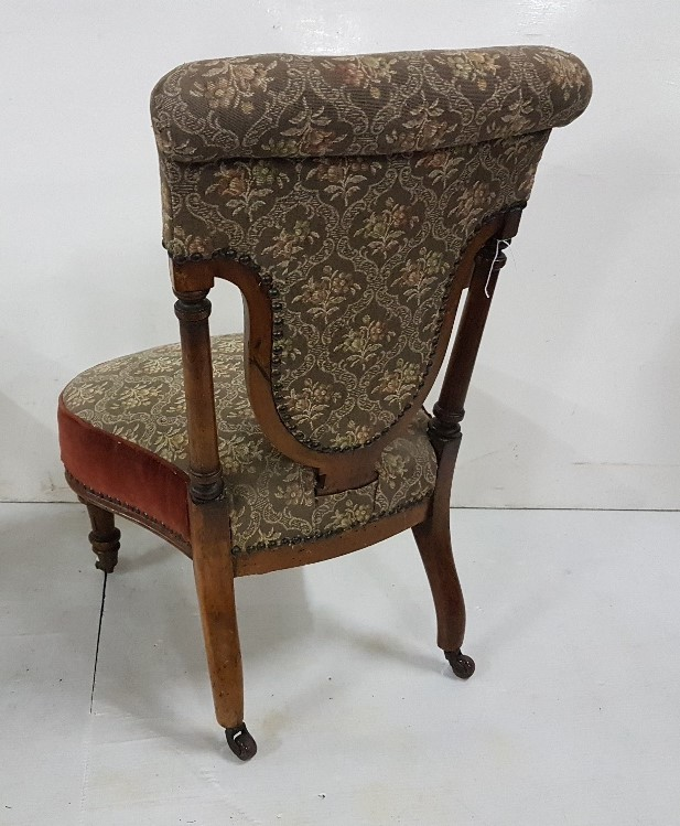 Lot 8 - A Victorian walnut low seat nursing chair with shaped seat and back, on turned & flutes supports
