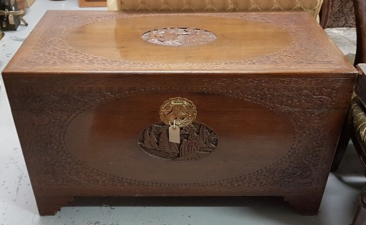 Lot 21 - A Chinese carved camphor wood coffer, with landscape scene to lid and front panel, shelf inside,