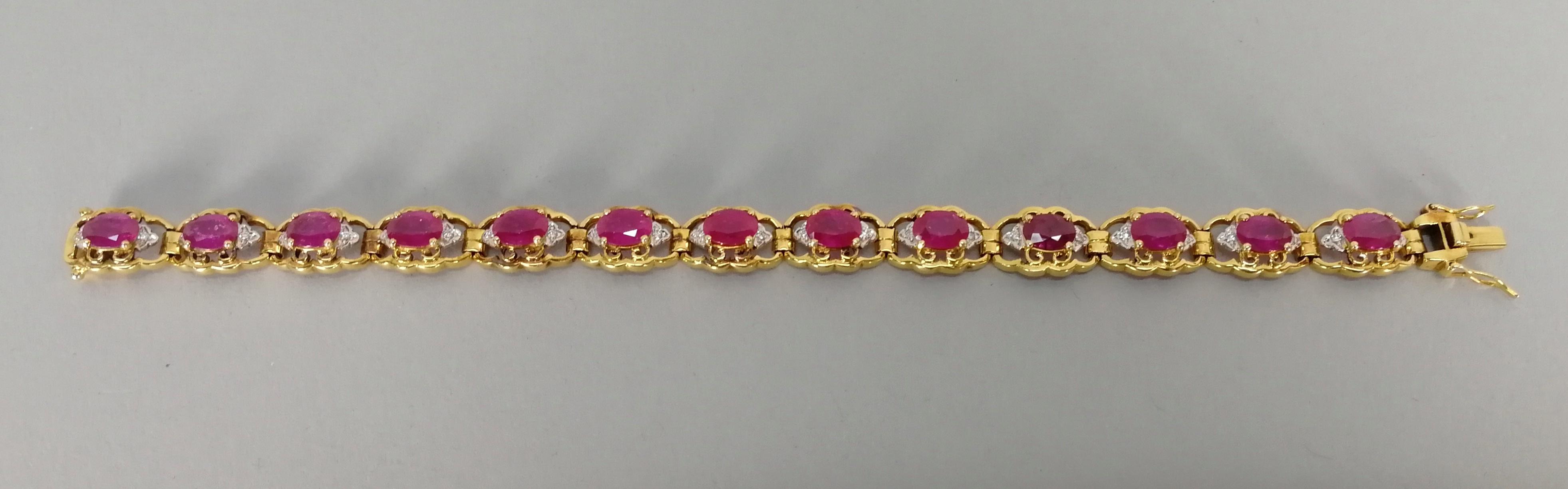 Lot 2 - Bracciale in oro bianco e giallo 18 kt. con tredici rubini contornati da piccoli diamanti, gr. 23