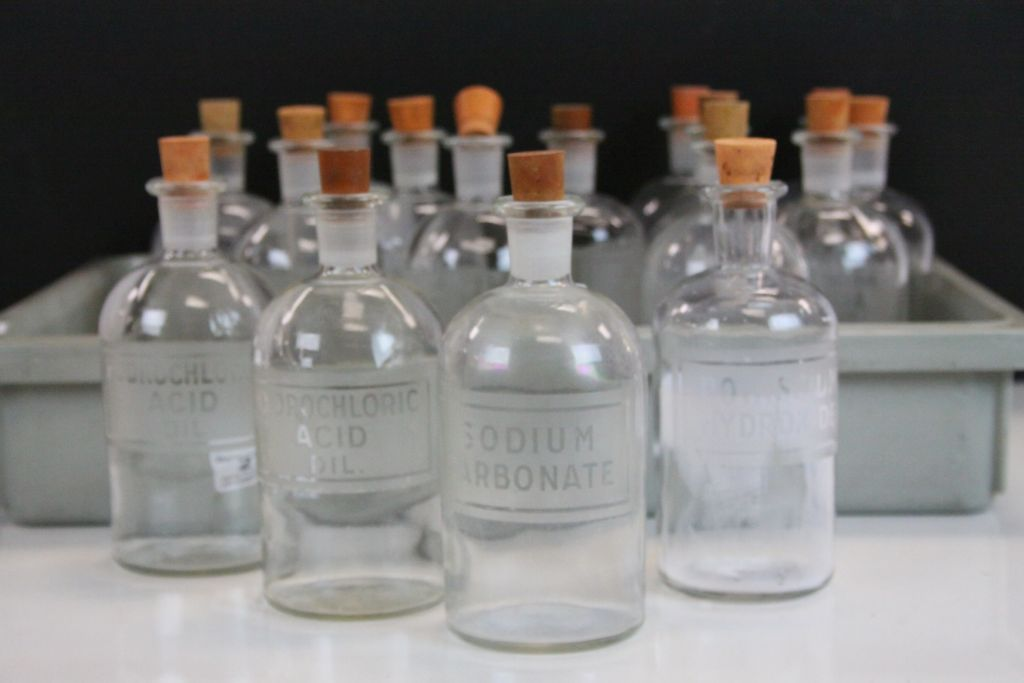 Lot 27 - 16 Glass Chemist Bottles with corks and Etched labels to include; Ammonium Hydroxide, Nitric Acid,