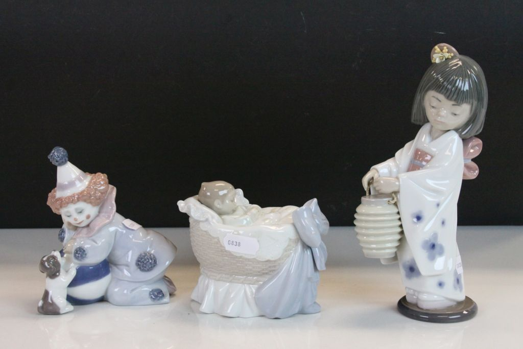 Lot 24 - Three boxed Lladro ceramic Figurines to include Oriental Girl, Clown with Puppy & Baby in a Crib