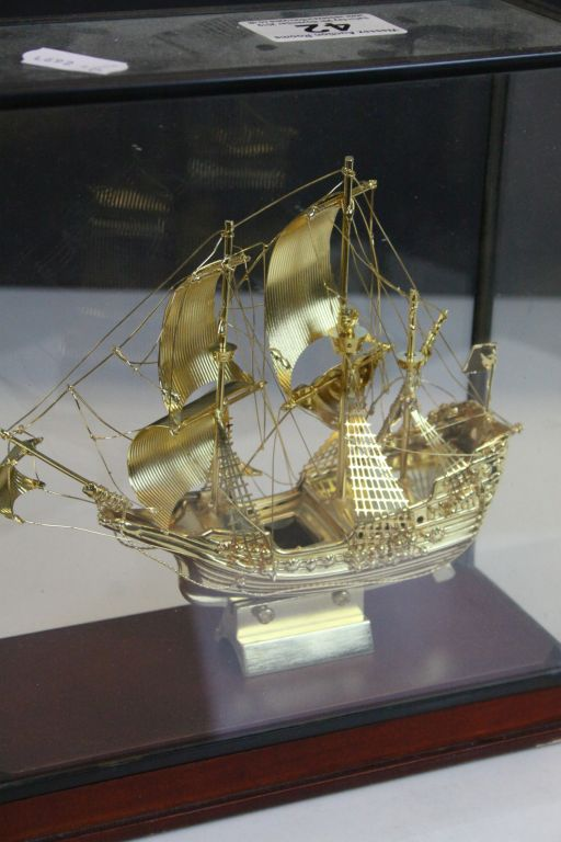 "Lot 42 - Glass cased Yellow metal model of the ship the ""Golden Hind"" with Wooden base, case approx 20 x 18.5"