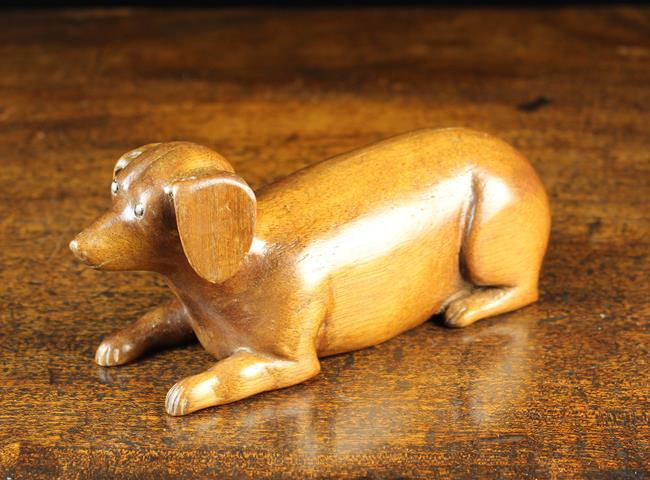 Lot 30 - A 20th Century Carved Mahogany Dog depicted lying down with inset nail head eyes,