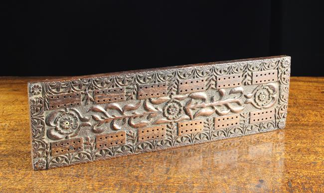 Lot 329 - A Fine 19th Century Carved Ebony Cribbage Board decorated with flowers and foliage defined against