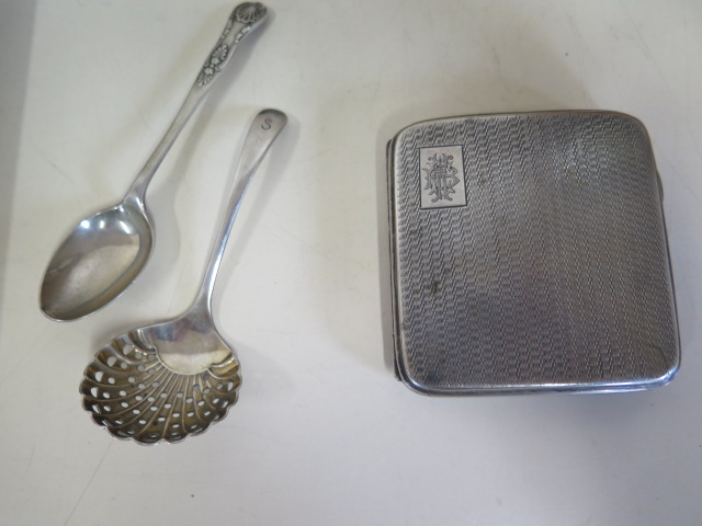 Lot 517 - A silver cigarette case, a silver spoon and a plated sifter, silver weight approx 3.5 troy oz