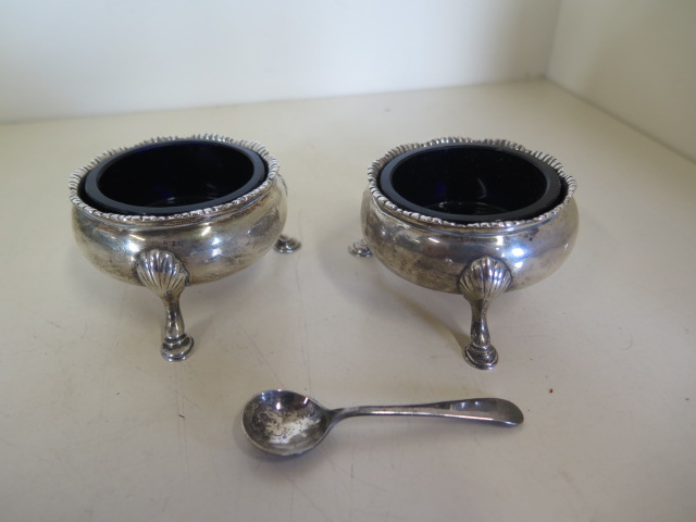 Lot 551 - A pair of Georgian silver salts standing on hoof feet with blue glass liners, hallmarked 1842 - by