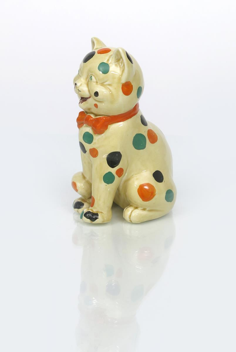 'Laughing Cat' a Clarice Cliff Bizarre figure, modelled seated and wearing a bow tie, painted with