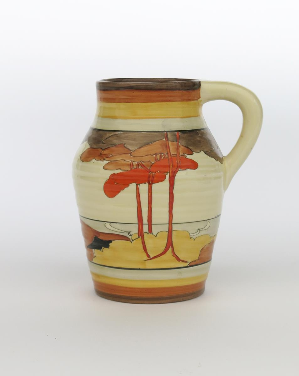 'Coral Firs' a Clarice Cliff Bizarre single-handled Isis jug, painted in colours between grey,