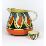 'Double V' a Clarice Cliff Bizarre Etruscan jug, painted in colours between yellow and orange bands,