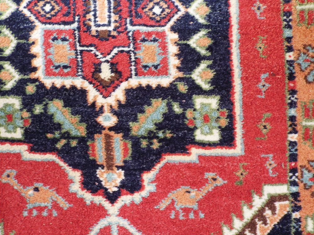 Lot 637 - Persian full pile rug with central navy blue medallion upon a red ground, 160 x 100 cm