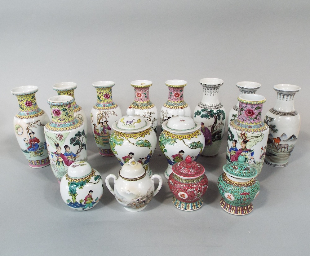 Lot 49 - A collection of modern oriental vases with various character and landscape decoration on a white