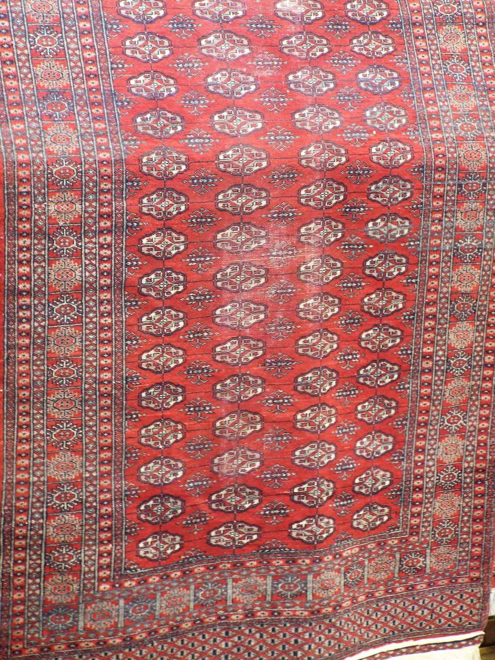 Lot 631 - Bokhara runner with typical geometric medallion decoration upon a red ground, 480 x 130 cm