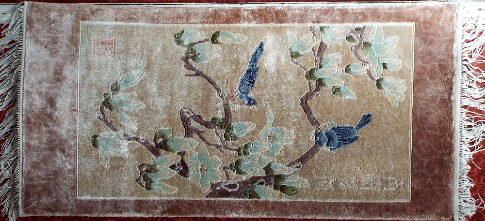 Lot 643 - A Chinese wool prayer mat size rug decorated with birds on branches upon an ivory ground, 130 x 60