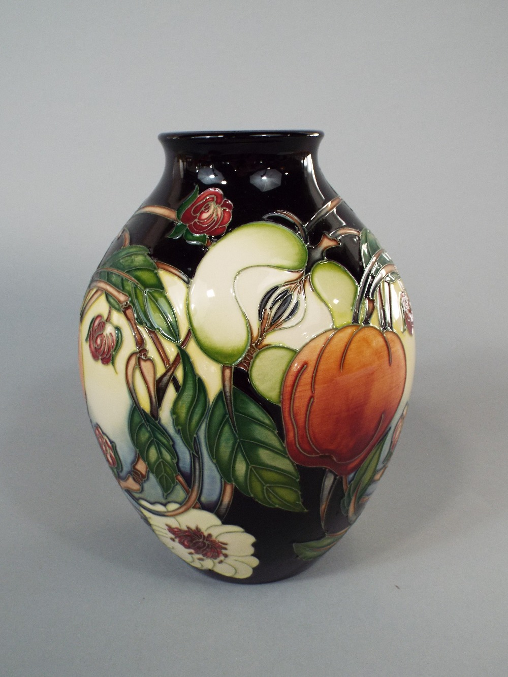 Lot 38 - A Moorcroft vase of ovoid form with painted fruit and floral detail, with impressed and printed