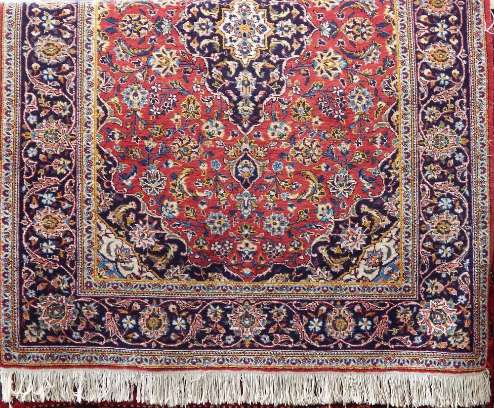 Lot 619 - Traditional Persian rug with central blue medallion framed by scrolled foliage upon a red ground,