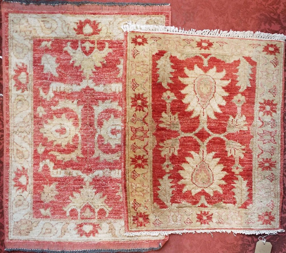 Lot 634A - Two small similar red and cream ground wool rugs with floral design 92 cm x 63 cm x 75 cm x 62 cm