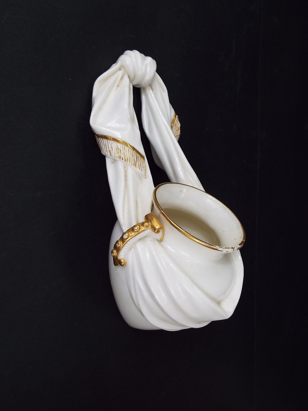 Lot 15 - A Royal Worcester ivory glazed wall pocket modelled as a vase supported by a fringed swag of