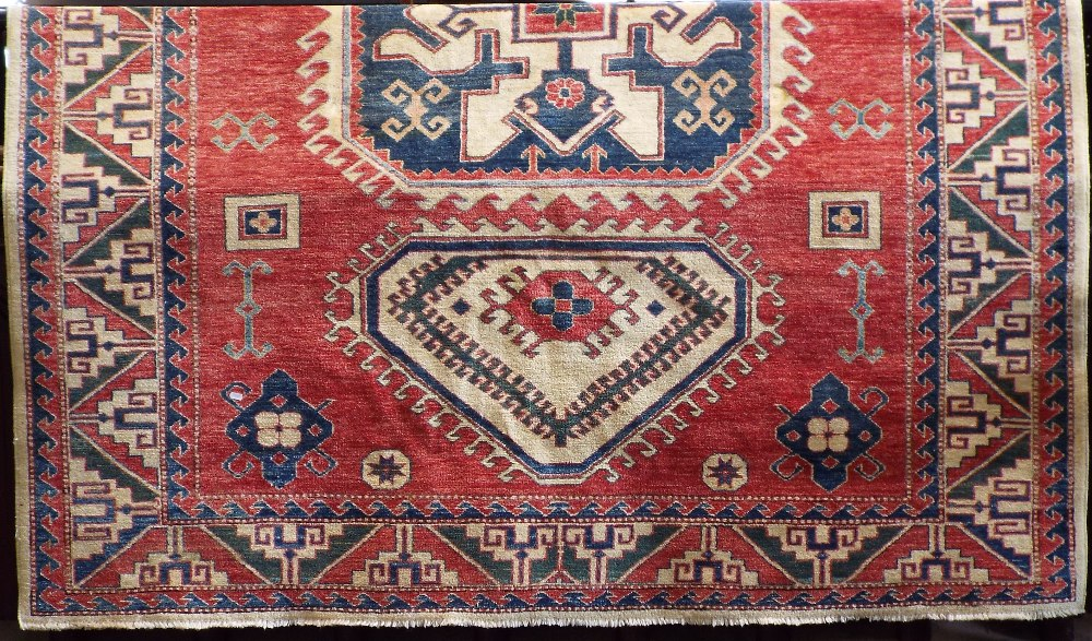 Lot 632 - Turkish carpet with three blue medallions upon a washed red and cream ground, 250 x 210 cm