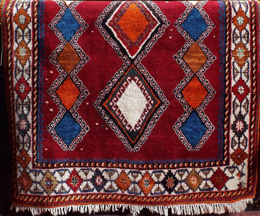 Lot 625 - Full pile Turkish rug with multi-coloured diaper decoration upon a red ground, 230 x 130 cm