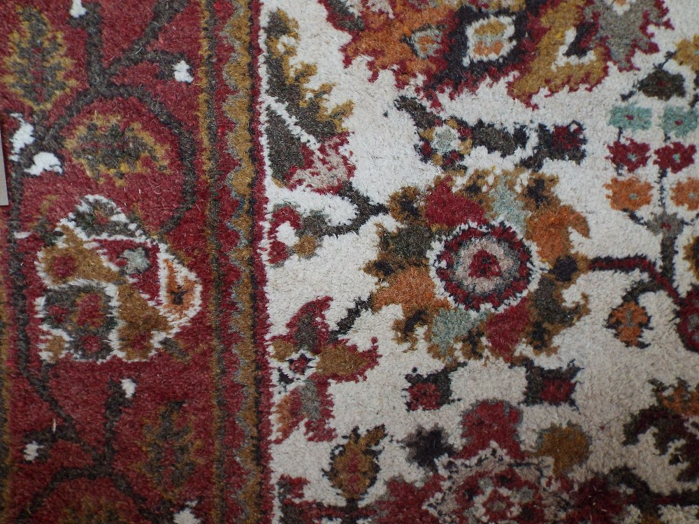 Lot 614 - Very full pile Eastern carpet decorated with floral sprays upon a cream ground with running red