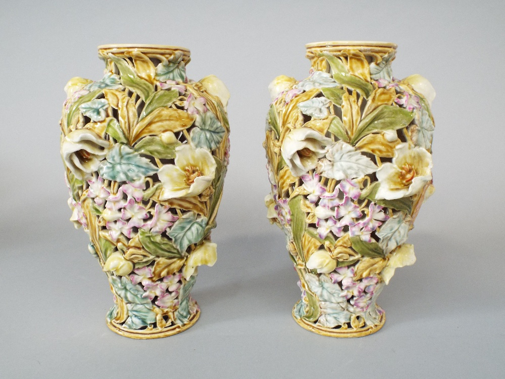 Lot 17 - A pair of Hungarian Zsolnay Pecs vases of pierced double skin form with all over floral detail and