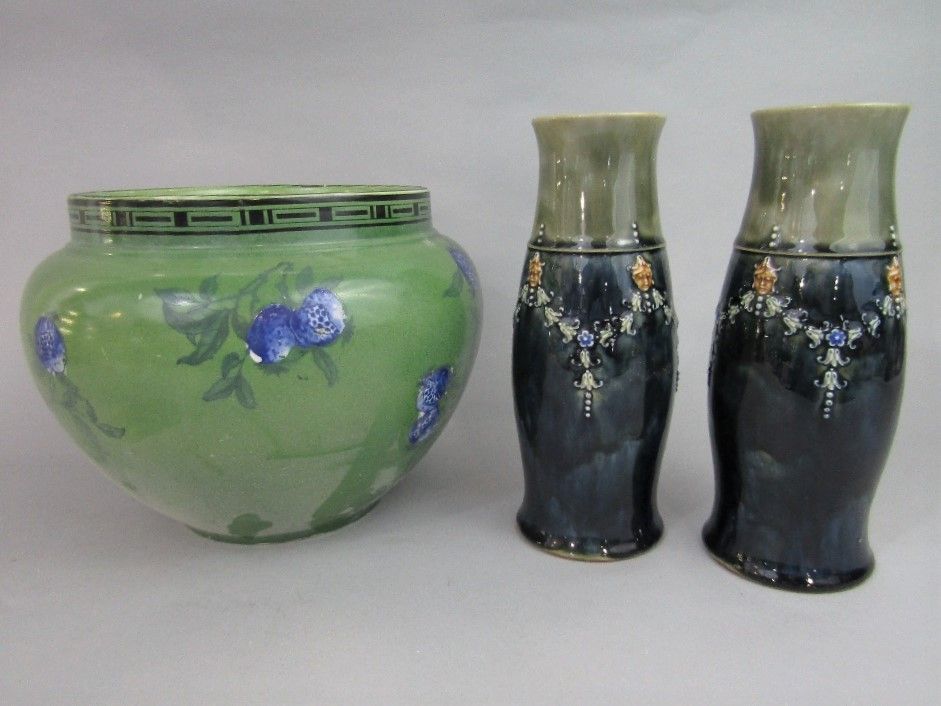 Lot 86 - A pair of Royal Doulton vases of curved cylindrical form with relief moulded mask and swag