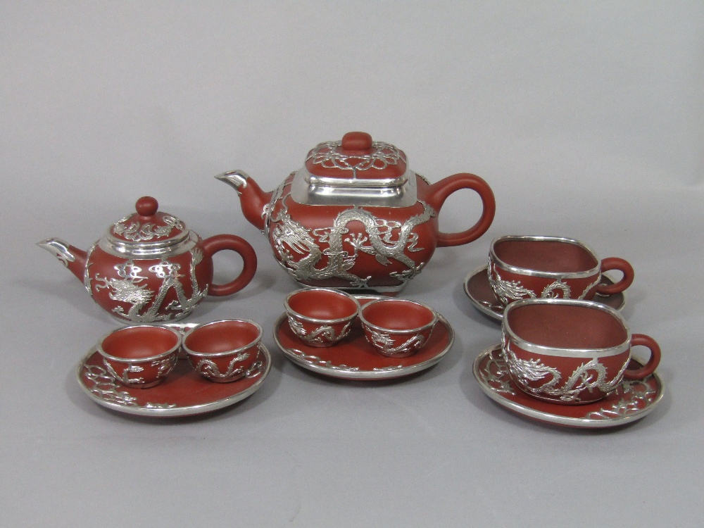 Lot 46 - A collection of oriental terracotta teawares with white metal overlay in the form of dragons,