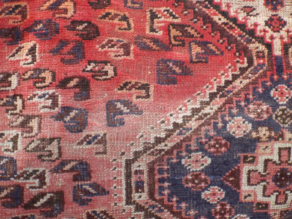 Lot 1421 - Middle Eastern rug with three central medallions framed by further Paisley scrolls upon a washed red