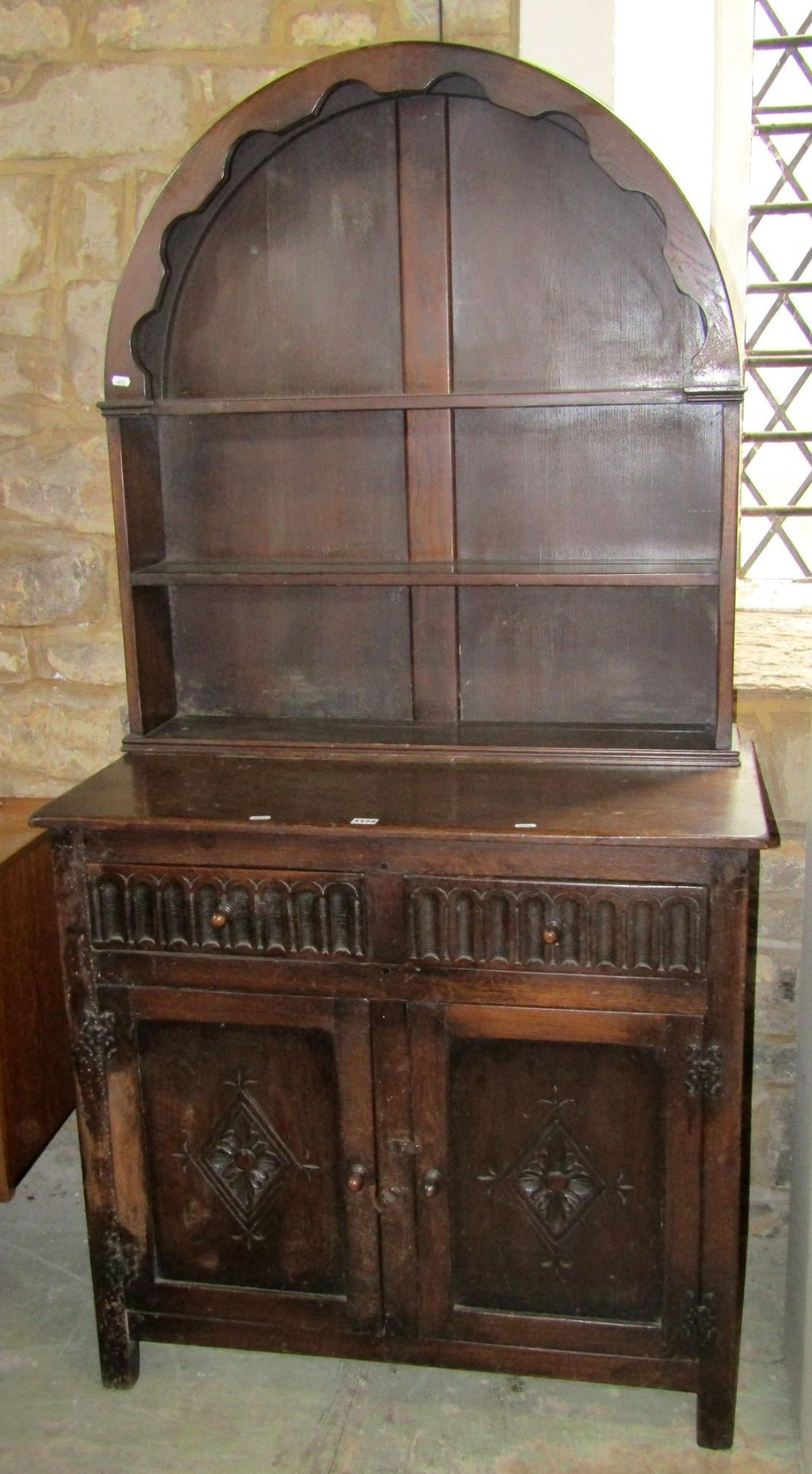 Lot 1173 - A small reproduction oak cottage dresser, the base enclosed by a pair of rectangular panel doors,