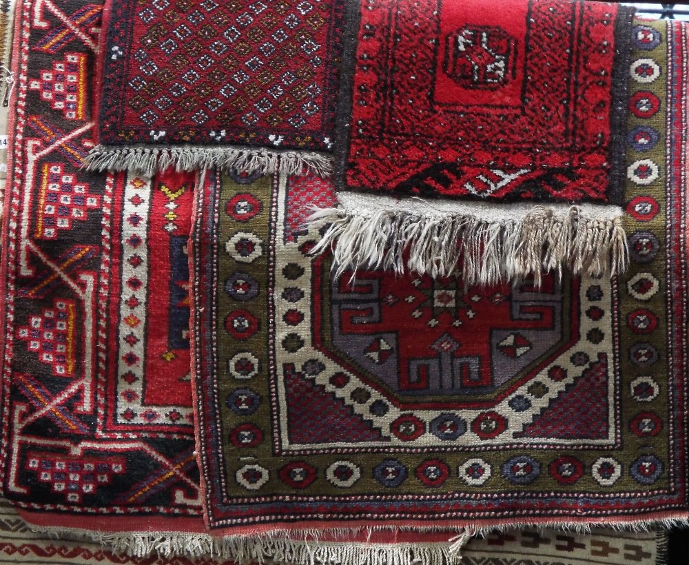Lot 1433 - Middle Eastern rug decorated with various medallions upon a red ground together with a similar green