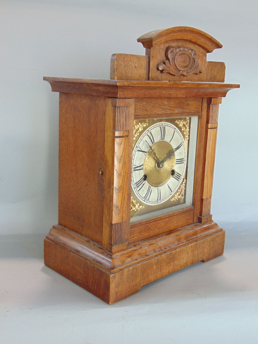 Lot 587 - Oak cased architectural two train mantel clock, the brass dial with silver chapter ring engraved