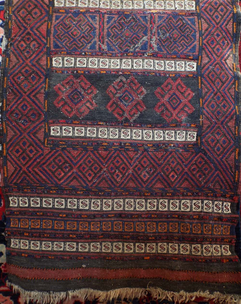 Lot 1415 - Old Kelim runner with typical geometric decoration upon a dark ground, 220 x 65 cm