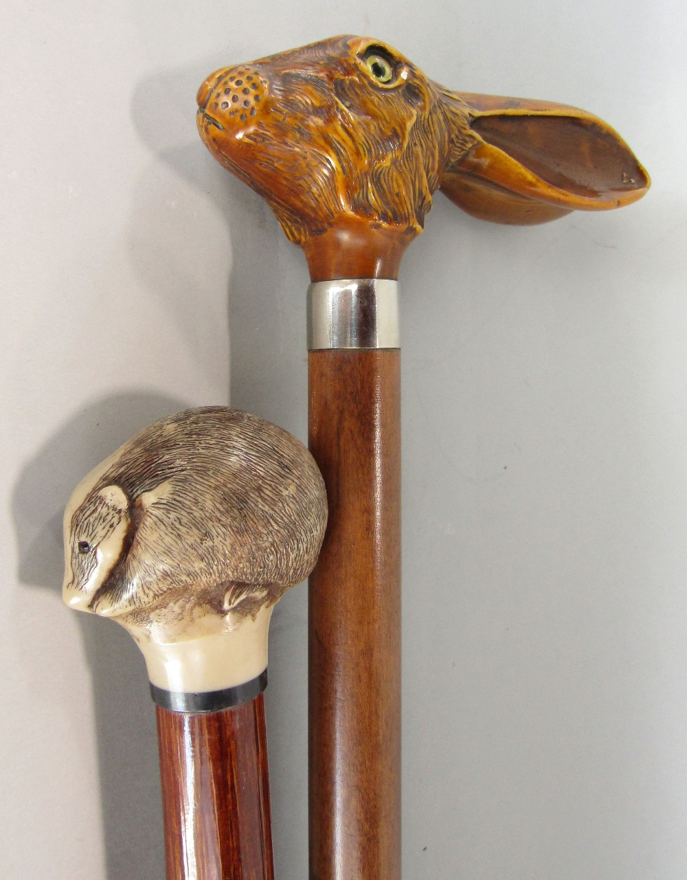 Lot 688 - A walking cane, the knop in the form of a hares head, another with a badger mount (both resin)